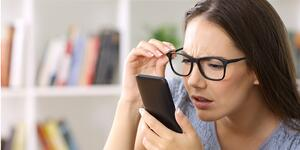girl-with-eyesight-problems-trying-to-read-phone-text-picture-id865753800